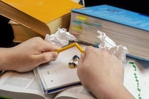 A frustrated student snapping their pencil over a pile of books. Having both anxiety and ADHD is hard.