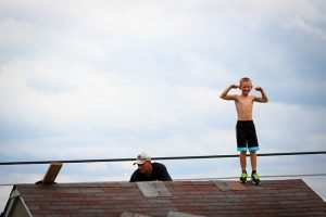 A boy standing on a rooftop while his dad fixes the roof